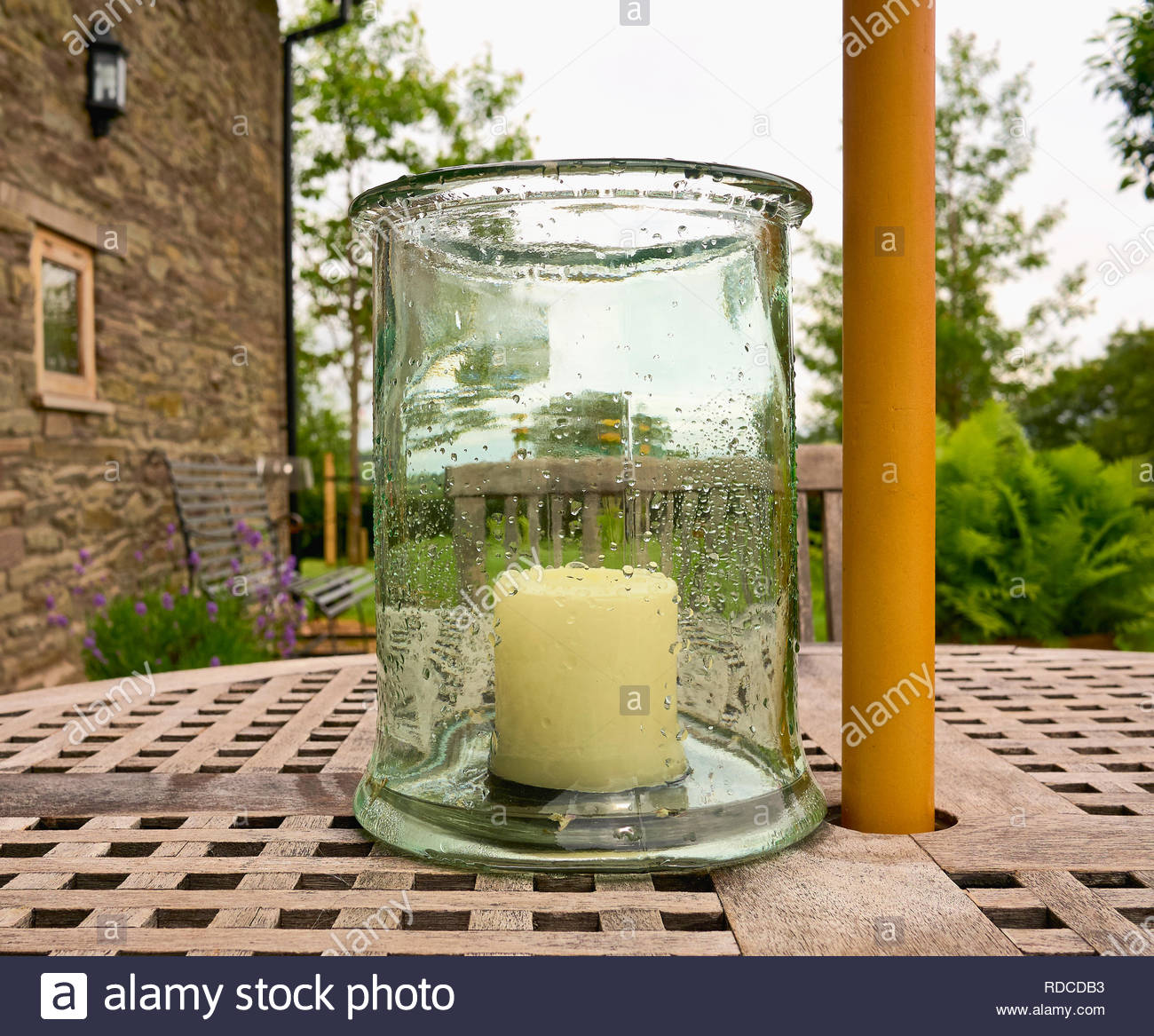 a large white unlit candle inside a glass jar covered with rain drops on a wooden patio table uk - Stock Image