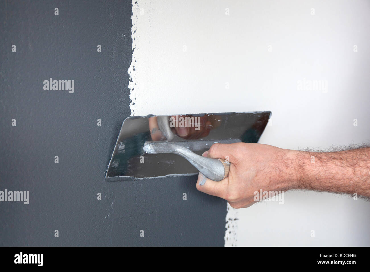 Hand with a trowel plastering a wall with decorative plaster Stock Photo