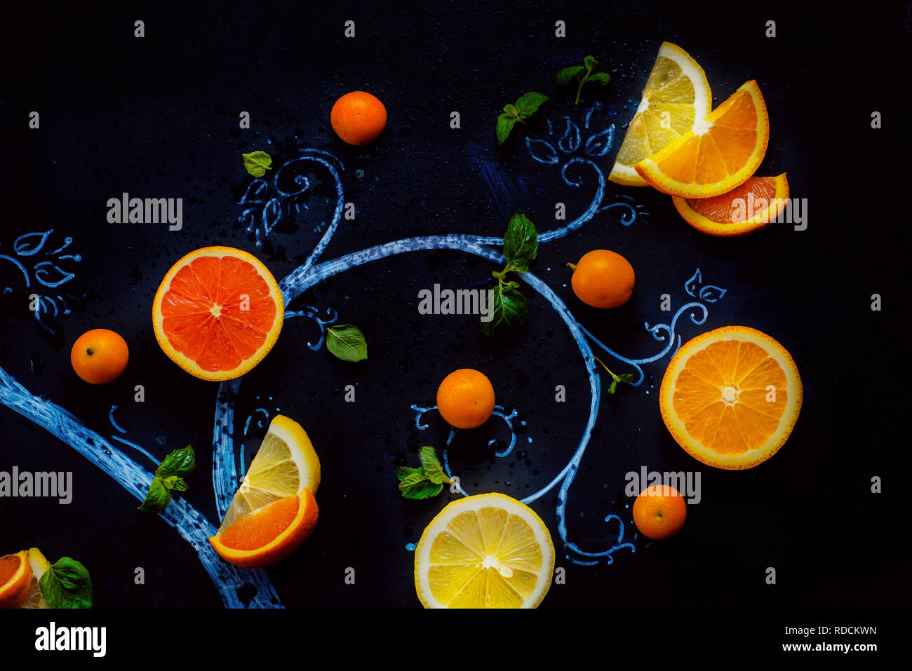 Lemon tea chalk tree with teacups, oranges and lemon slices, mint leaves and kumquats. Hot drink creative flat lay on a dark background with copy space - Stock Image