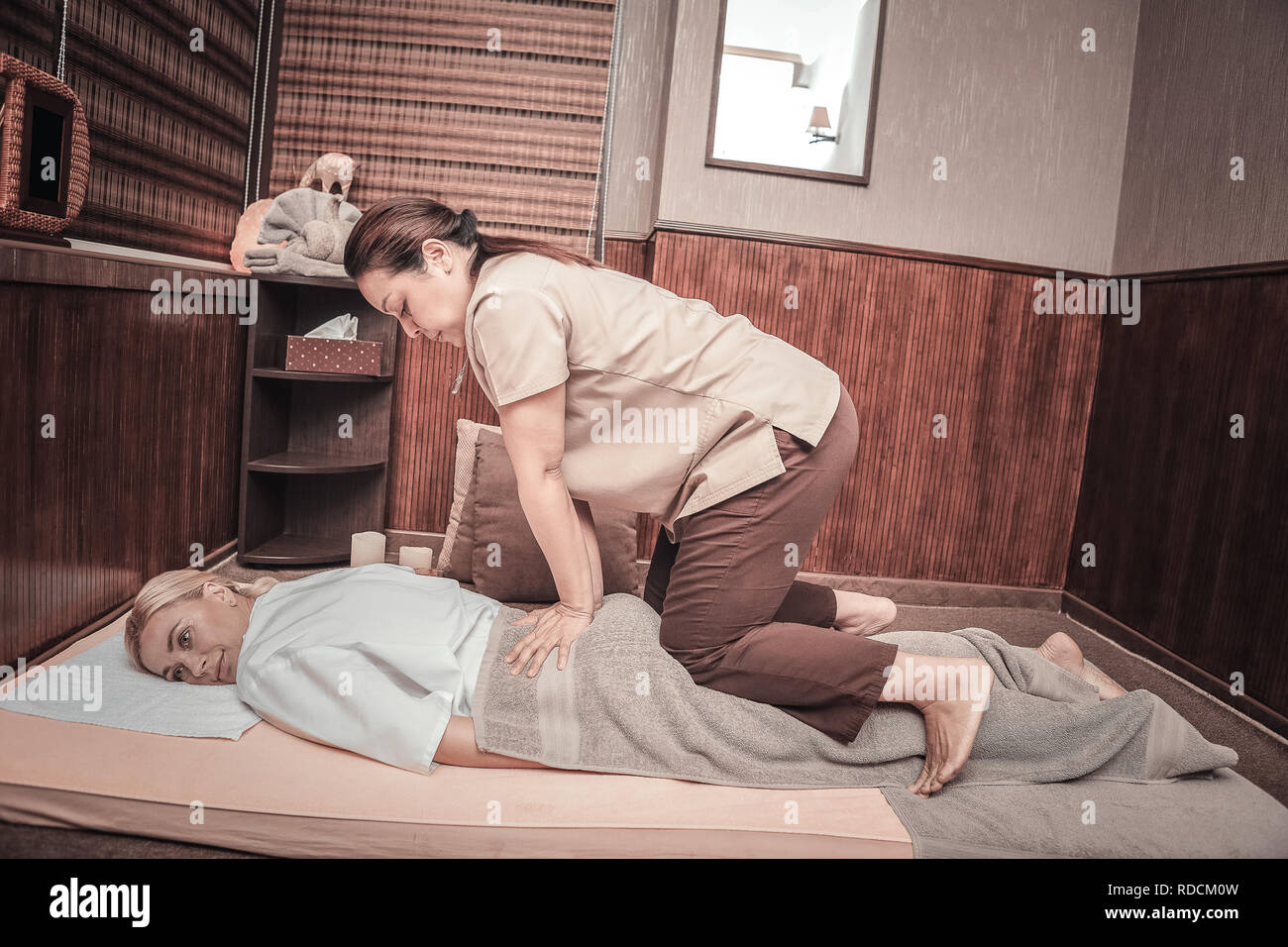 Nice young woman having special Thai massage Stock Photo