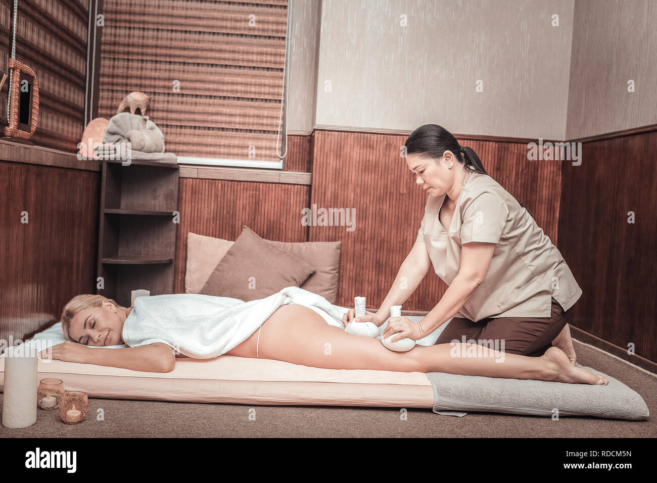 Nice skilled masseuse massaging her clients body - Stock Image