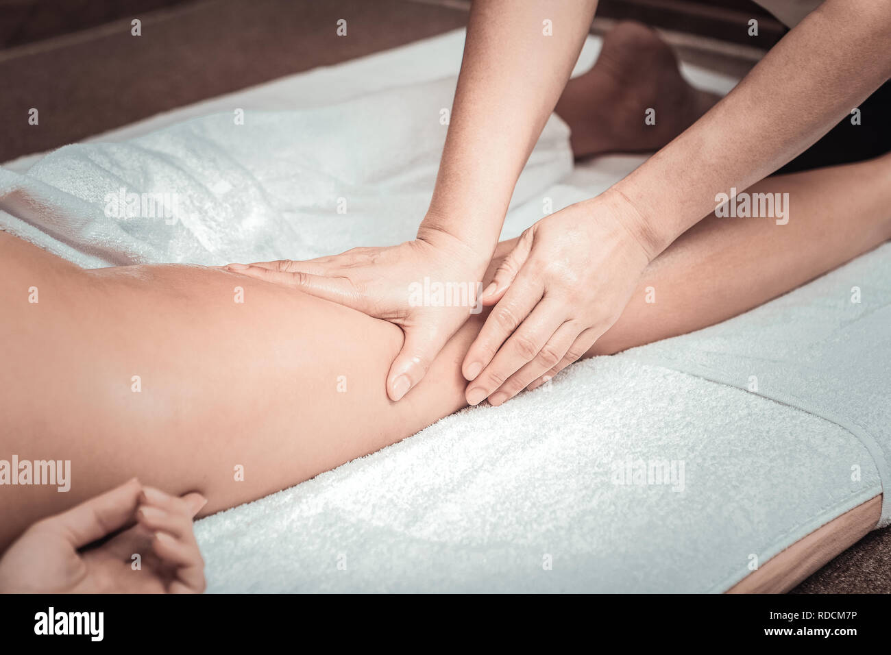 Professional female masseuse touching her clients leg - Stock Image