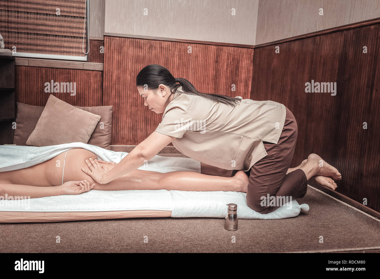 Serious female masseuse massaging her clients body Stock Photo
