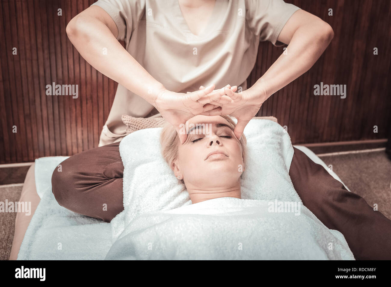 Nice professional female masseuse massaging the temples - Stock Image