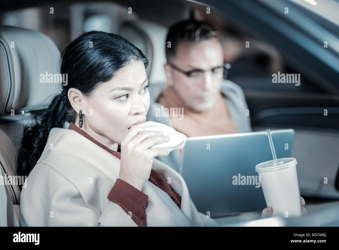 Husband and wife eating junk food sitting in their car - Stock Image