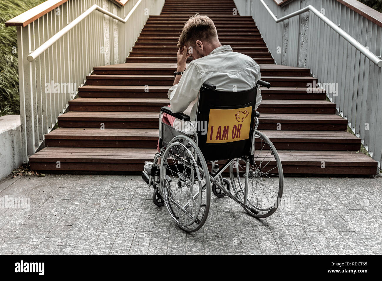 Upset young man sitting in his wheelchair - Stock Image