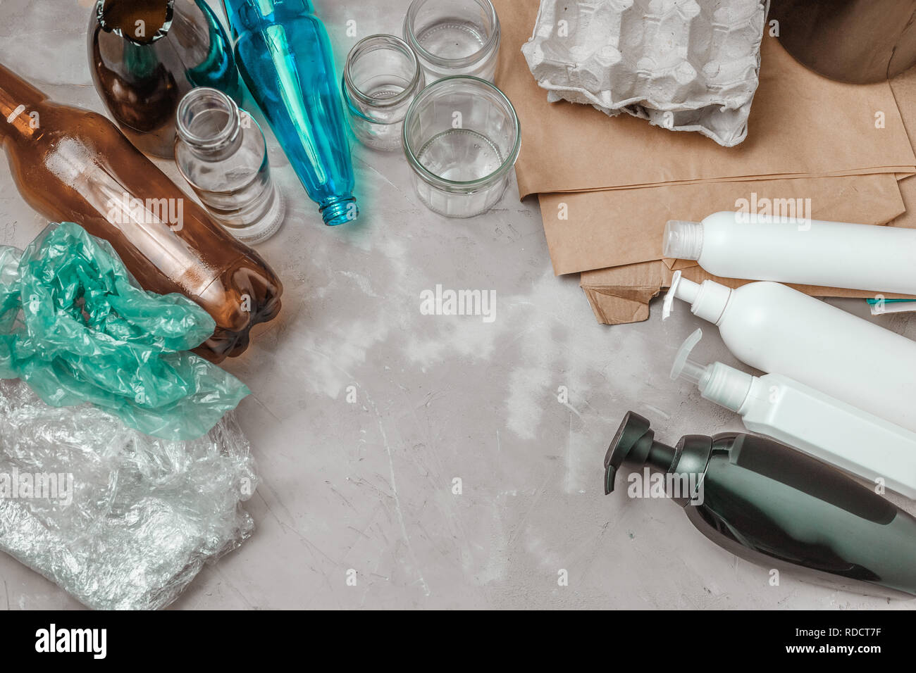 Differnt types of waste, plastic bag, crumpled paper, plastic containers, glass and bottles on the table. Management waste sorting concept Stock Photo