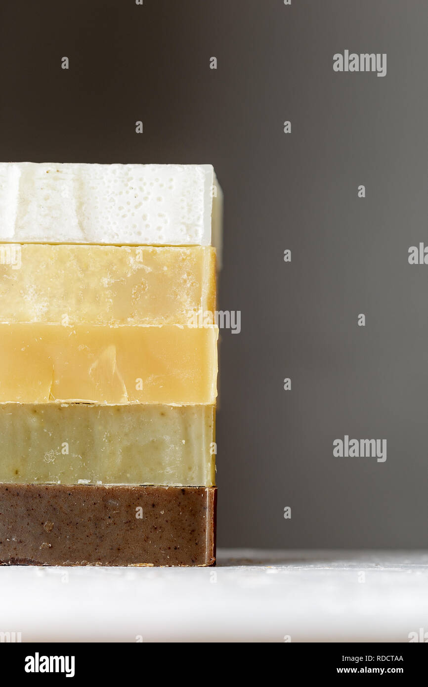 Tower stack of different kinds of handmade soaps over grey background Stock Photo