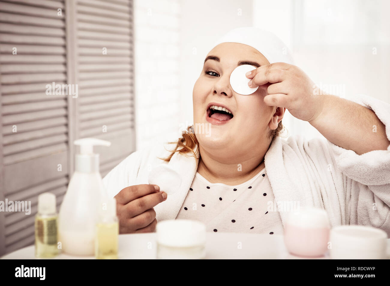 Contented overweight woman using cotton pad for removing - Stock Image