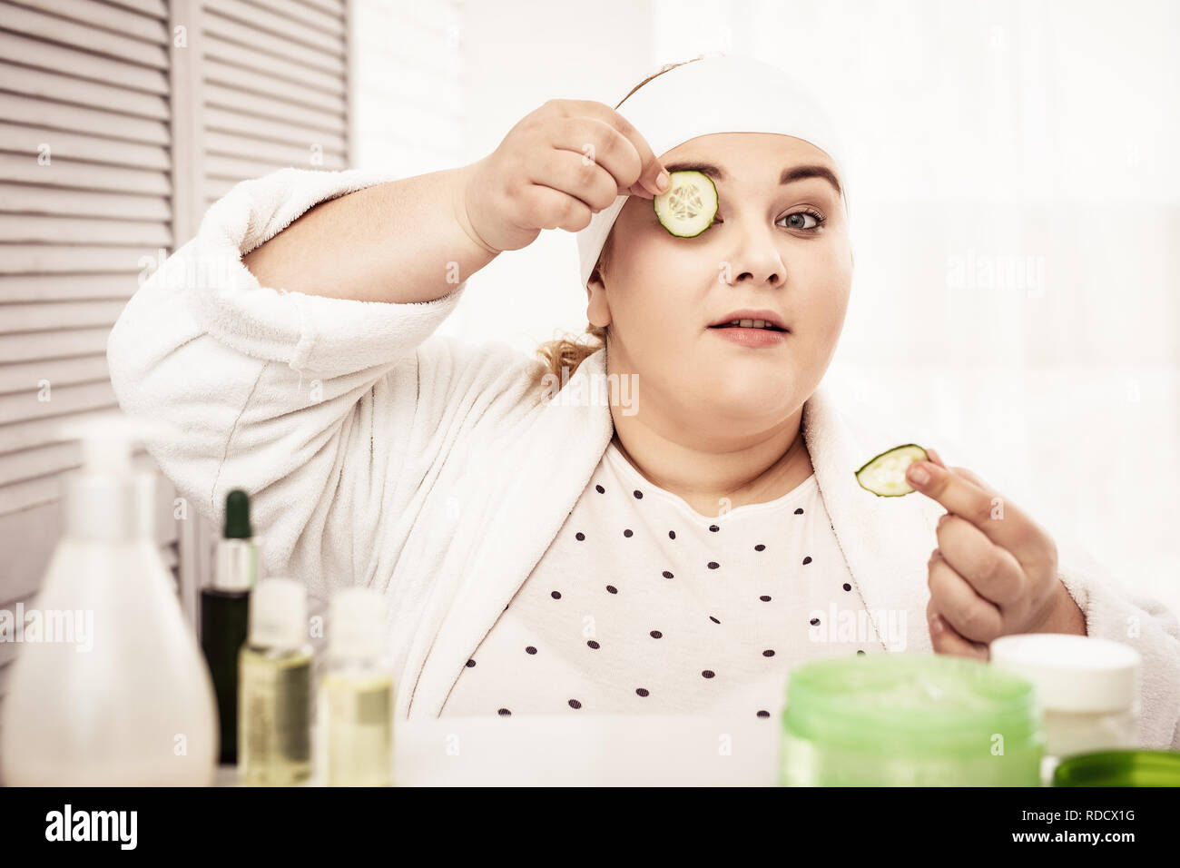Focused big woman putting cucumbers on her eyelids - Stock Image