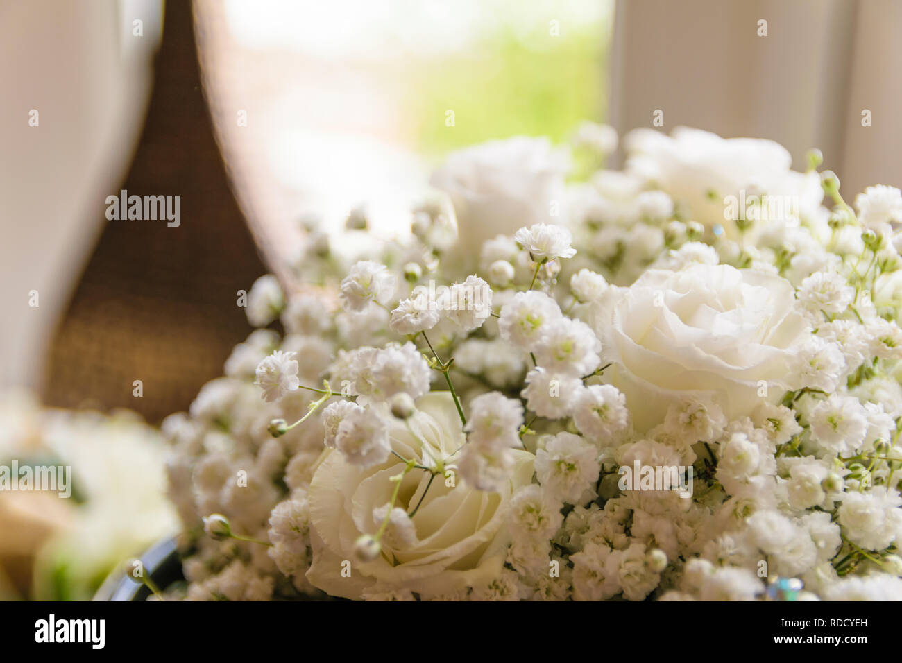 A bouquet of wedding flowers, the white roses shining in the sunlight through the window. - Stock Image