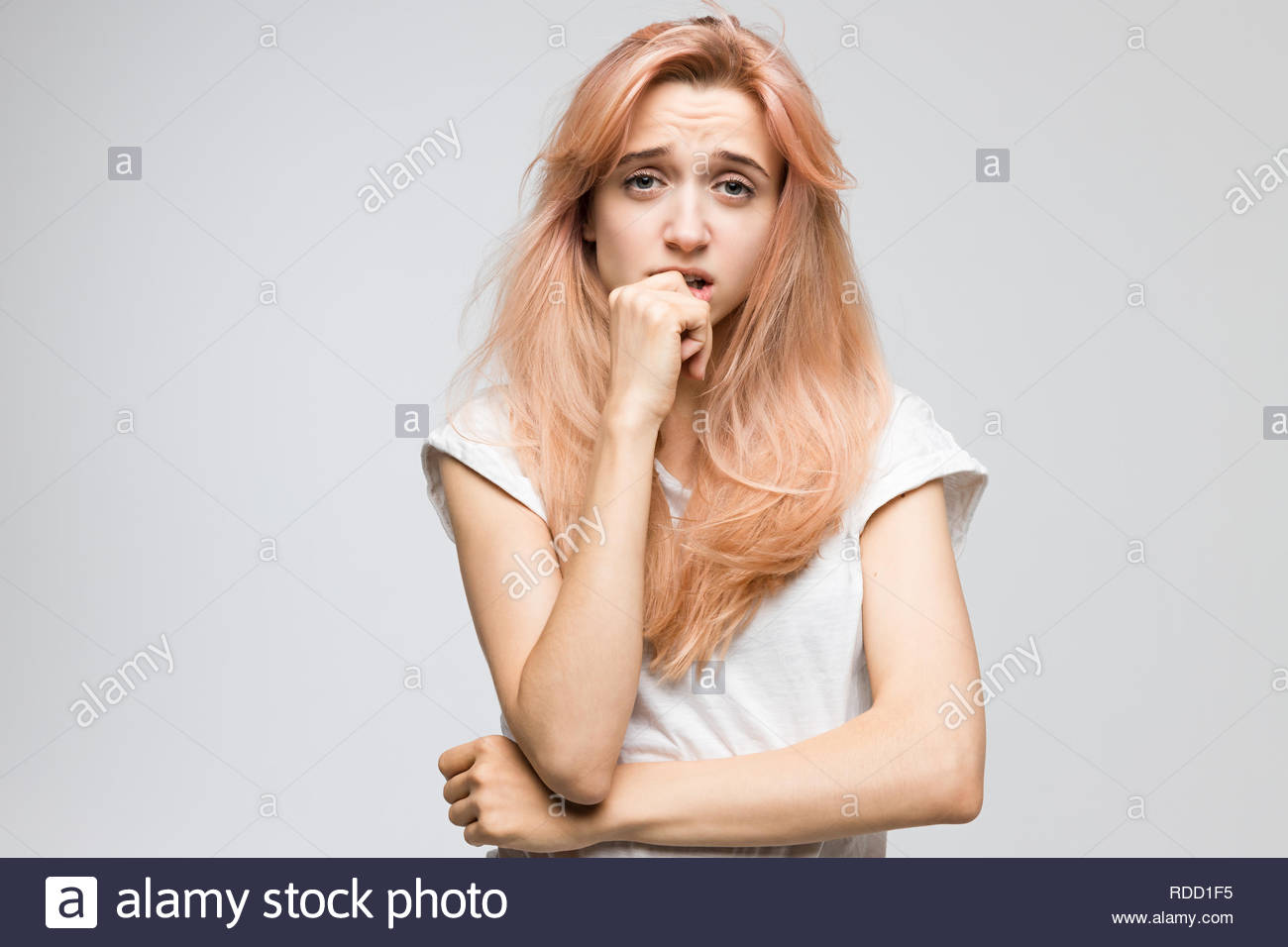 Cropped studio portrait of cute blonde girl in white t-shirt looks with bewilderment and disappointment/closed posture, angry. - Stock Image