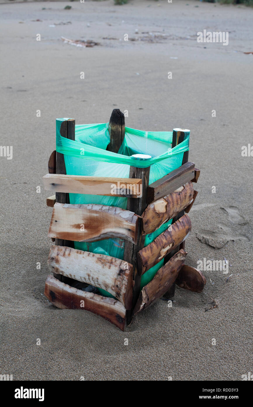 A trash can on a beach - Stock Image