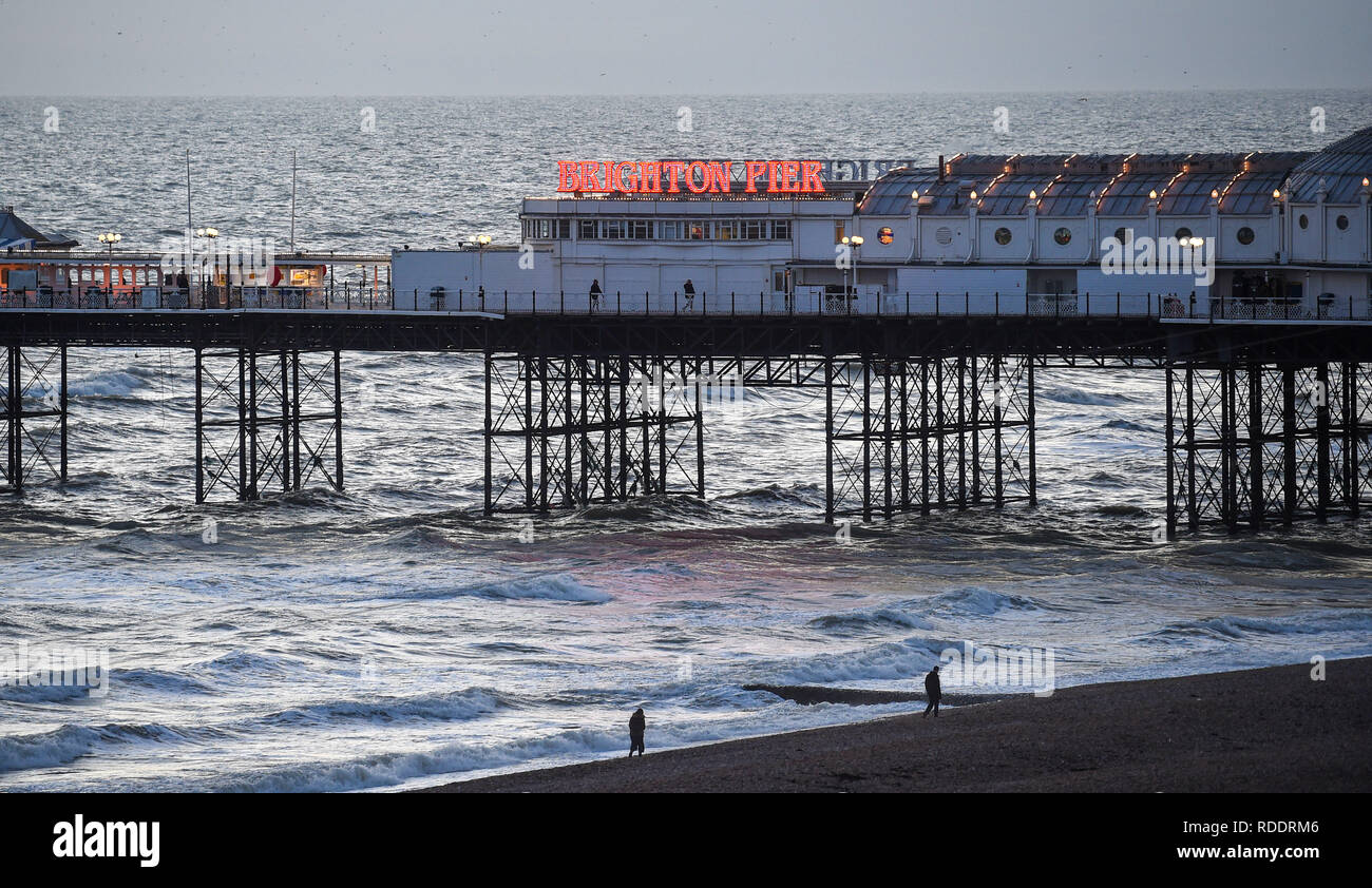 Brighton UK 18th January 2019 - UK Weather: A couple of walkers brave the chilly wind on the beach by Brighton Palace Pier as the cold weather is forecast to continue throughout Britain over the next few days Credit: Simon Dack/Alamy Live News - Stock Image