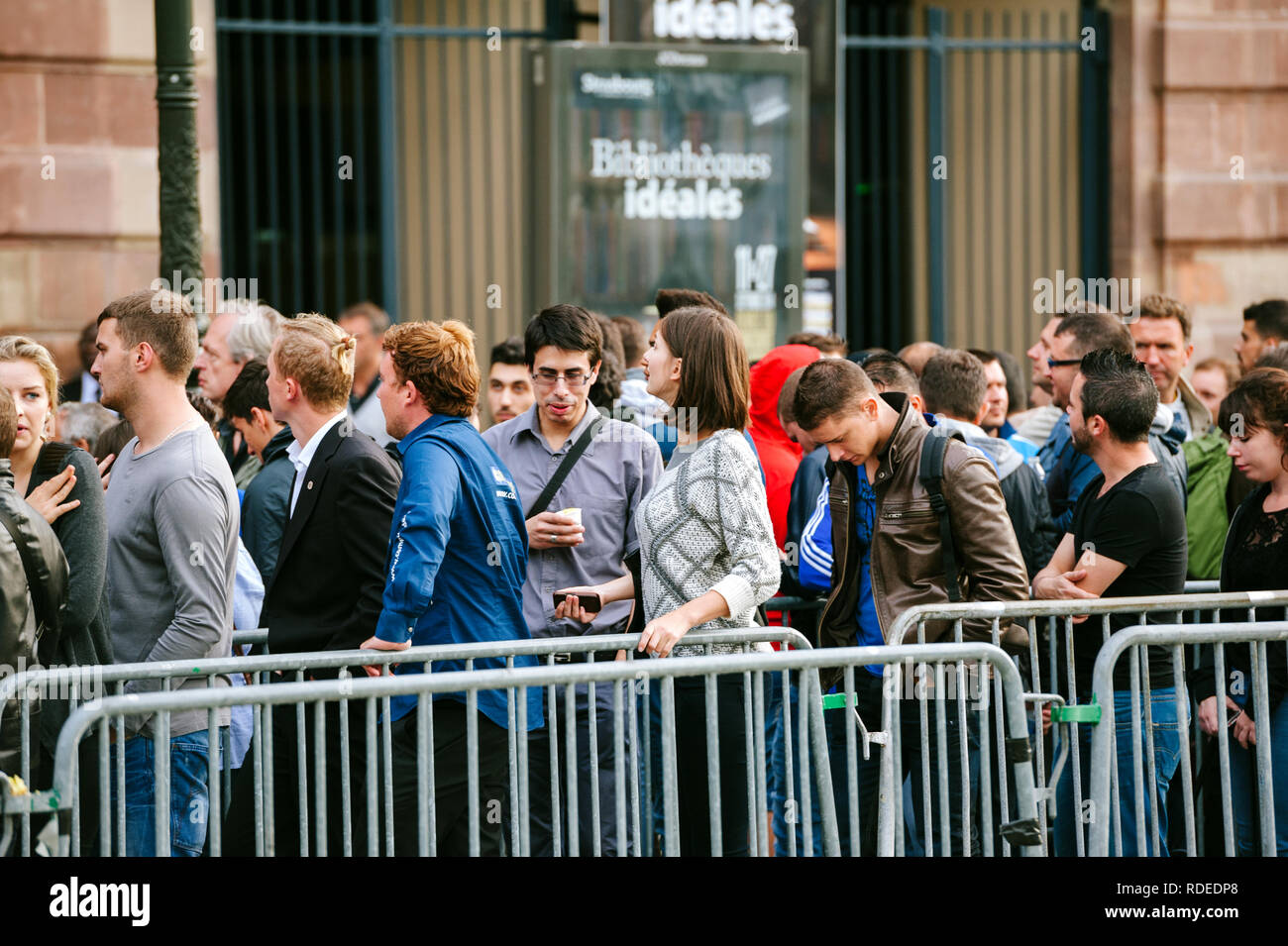 STRASBOURG, FRANCE - SEP, 19 2014: Large queue in front of Apple Store with customers waiting in line to buy the latest iPhone iPad Apple Watch and notebook Stock Photo