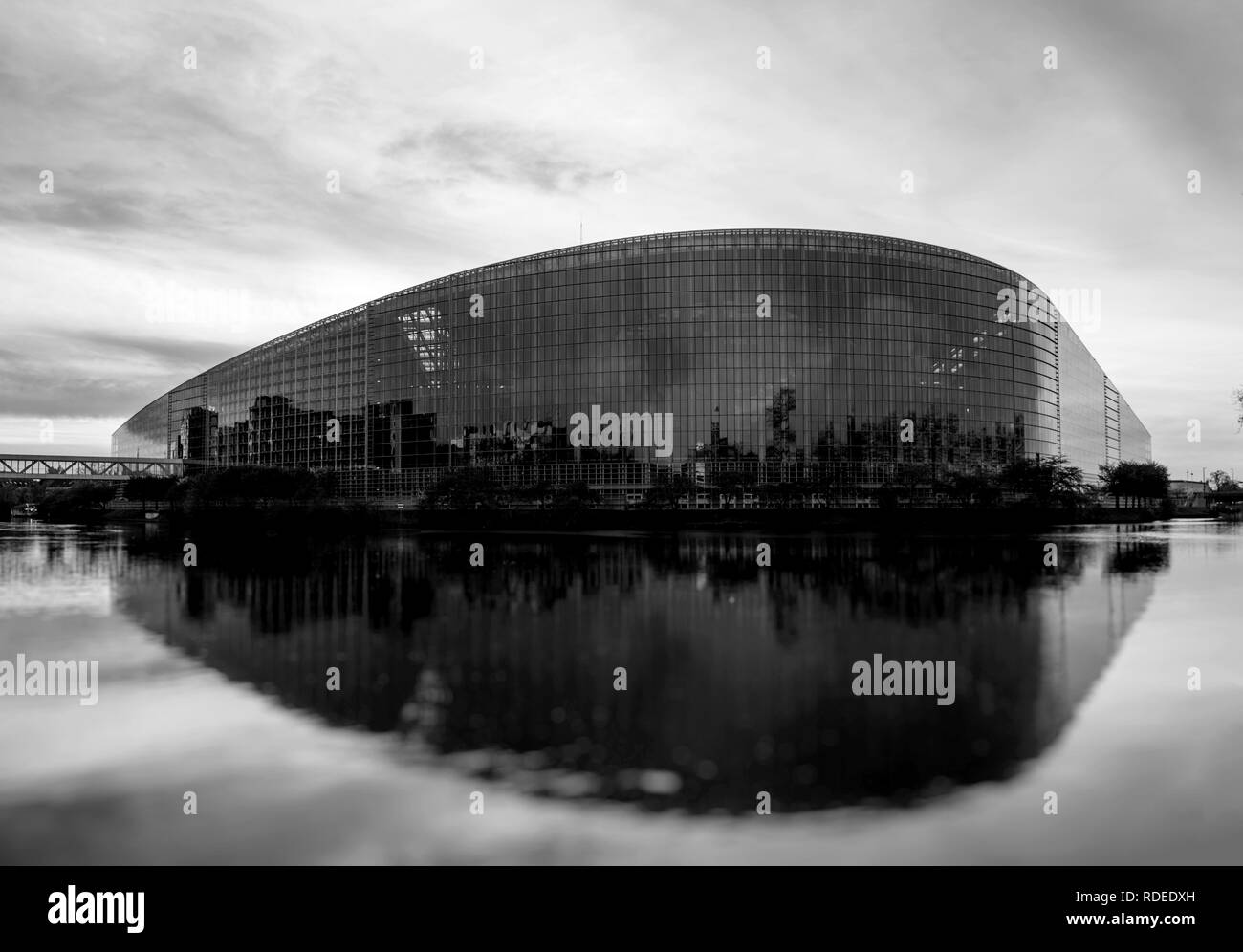 STRASBOURG, FRANCE - MAR 31 2017: Black and white image of South facade of the European Parliament in Strasbourg with the intersection of the Ill and Marne-Rhine Canal at dusk. The European Parliament or EU Parliament or the EP is the directly elected parliamentary institution of the European Union EU  - Stock Image
