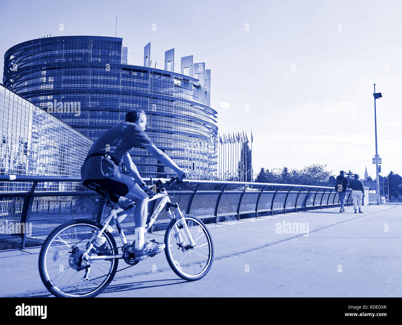 STRASBOURG, FRANCE - AUG 20, 2016: Blue color toned chromacity of senior cyclist sport workout in front of the european parliament building in Strasbourg on a calm summer day  Stock Photo