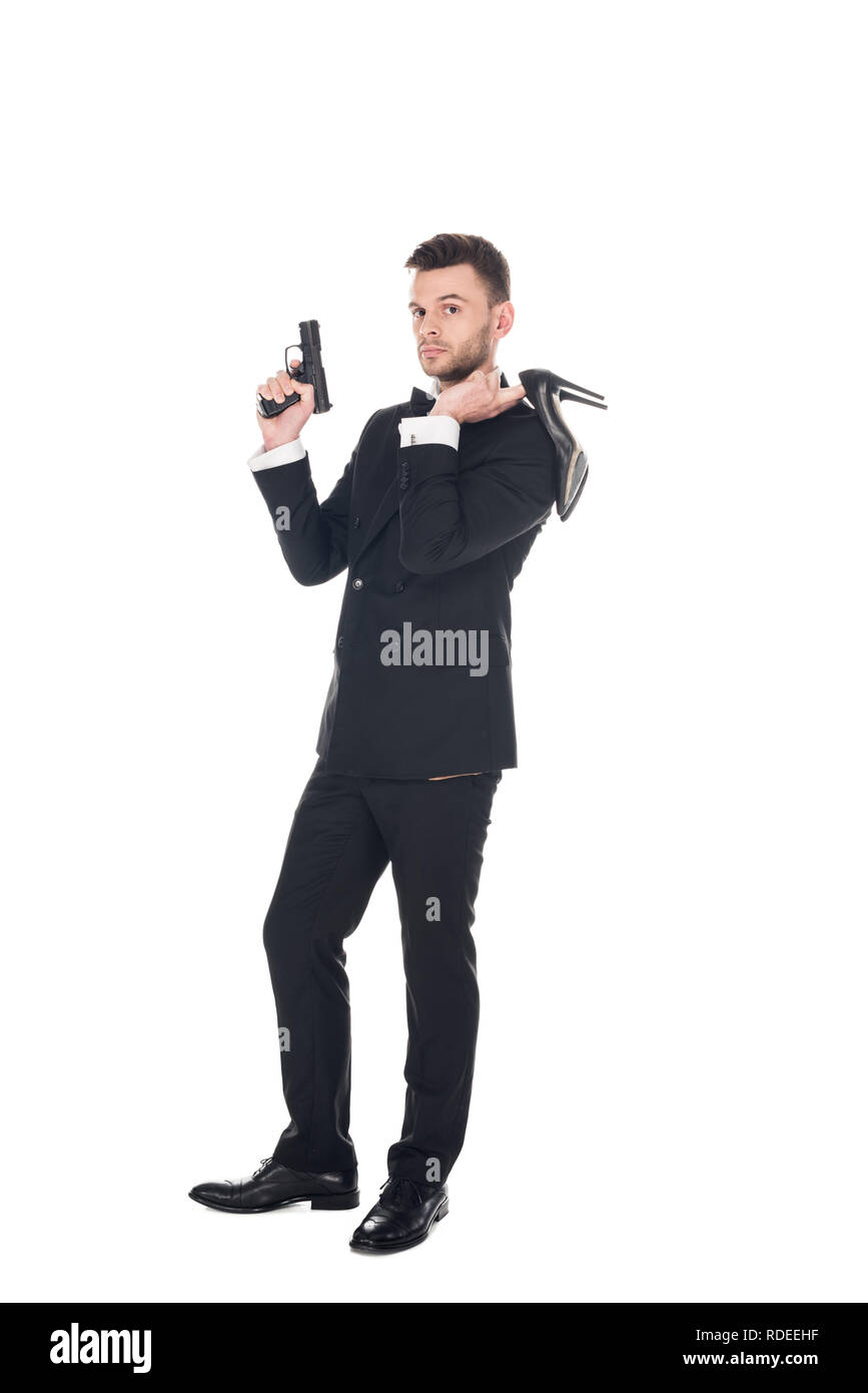 elegant secret agent in black suit holding handgun and high heels, isolated on white - Stock Image