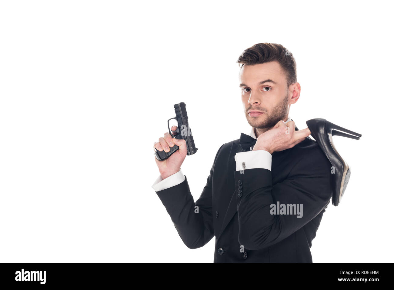 handsome secret agent in black suit holding handgun and high heels, isolated on white - Stock Image