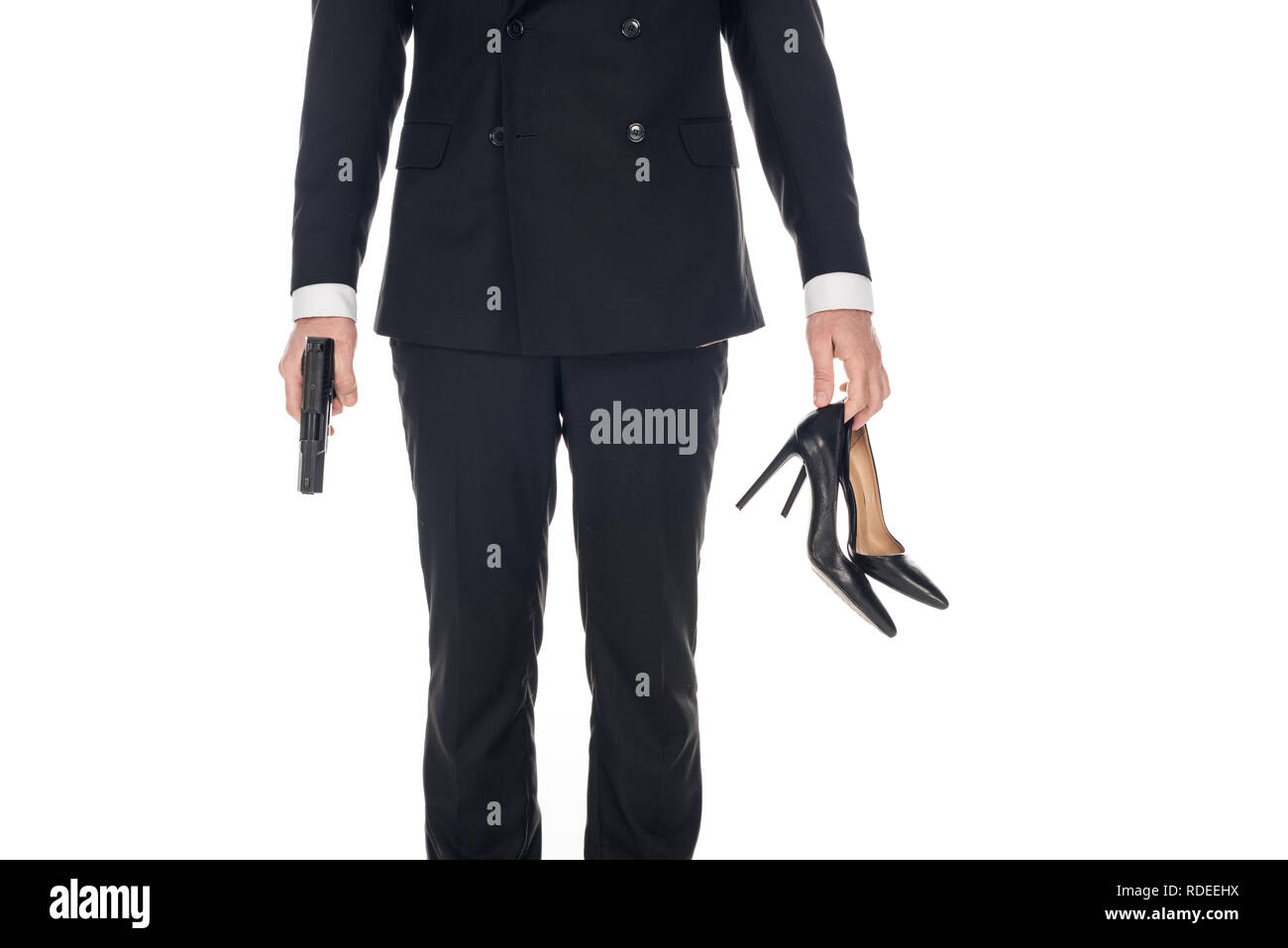cropped view of killer in black suit holding handgun and high heels, isolated on white - Stock Image