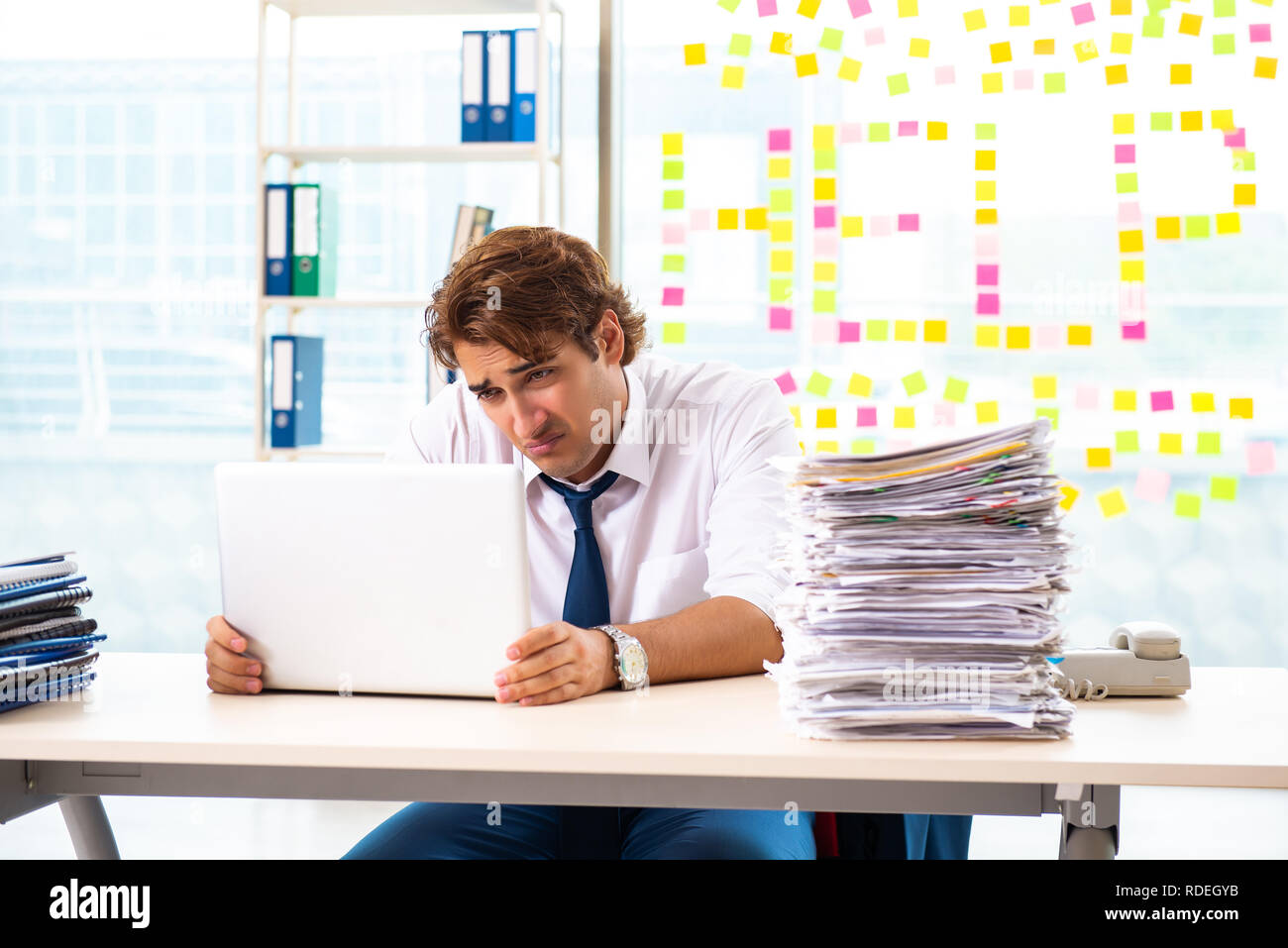 Busy businessman working in the office - Stock Image