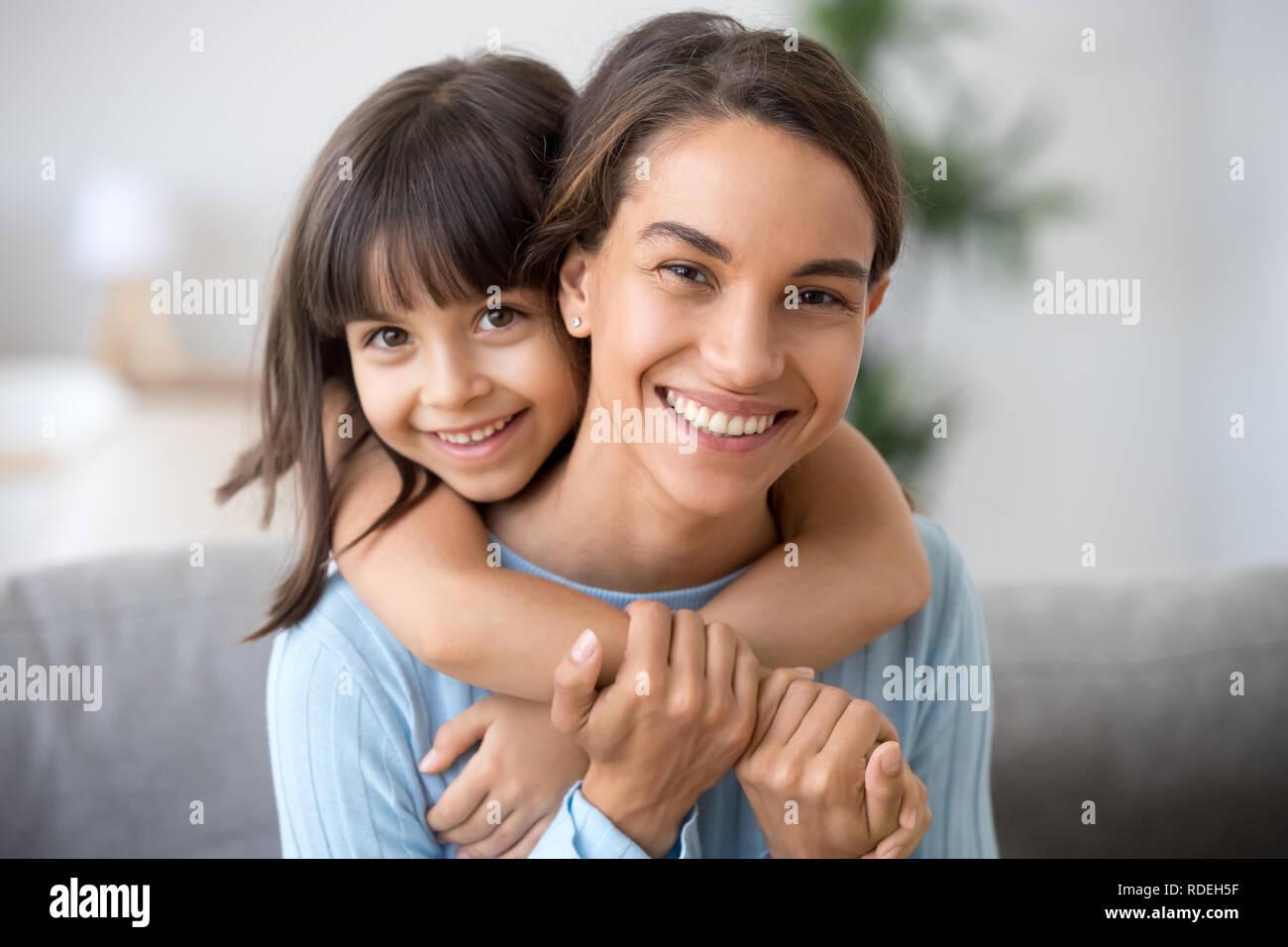 Happy mom and cute kid daughter embracing looking at camera - Stock Image