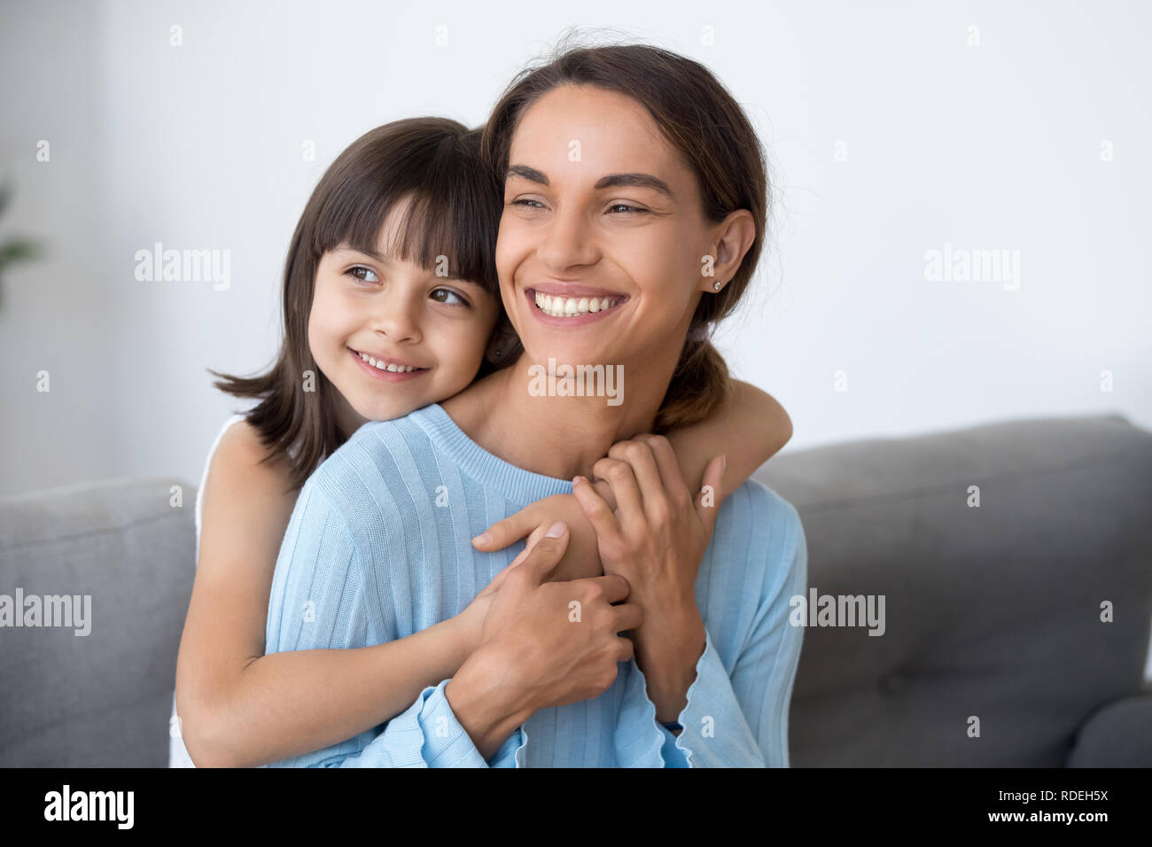 Smiling mom and cute kid daughter embracing looking into future - Stock Image