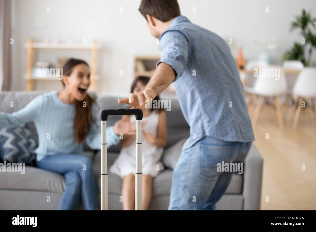 Wife and kid excited to meet dad arriving from trip - Stock Image