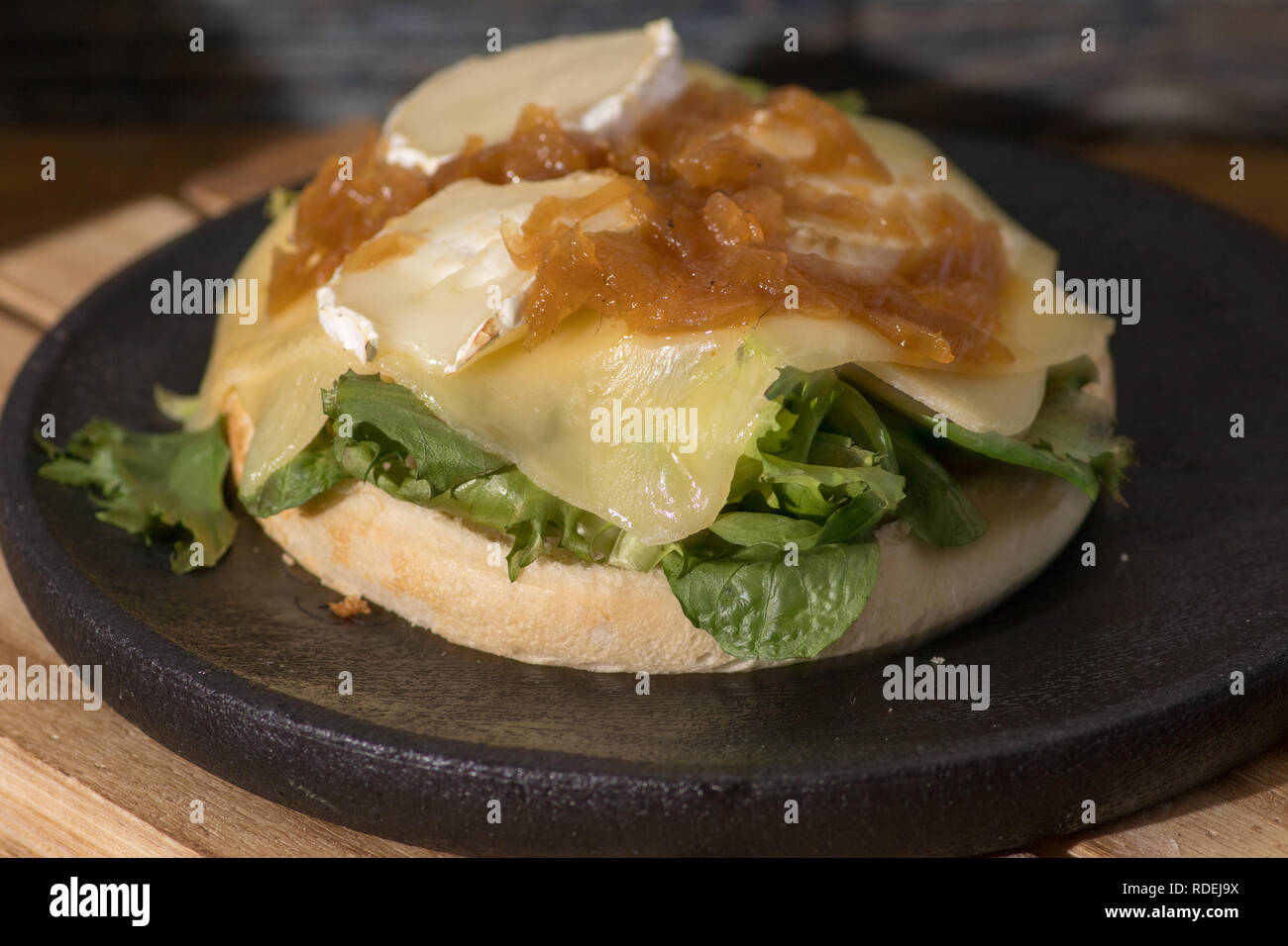 vegan hamburger with cheese and ketchup on black wooden plate Stock Photo