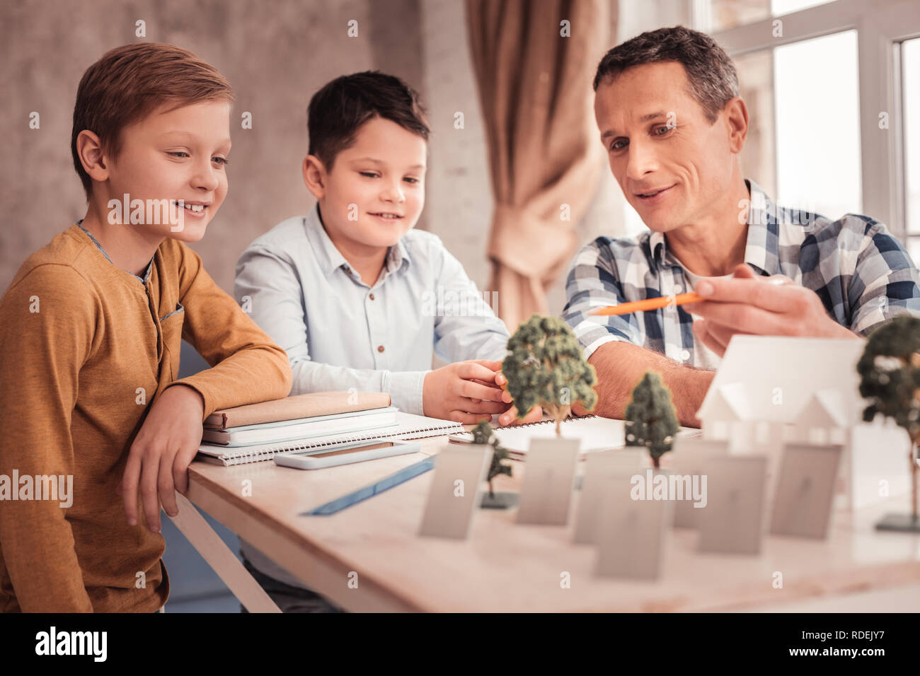 Smiling foster father feeling cheerful spending time with children - Stock Image