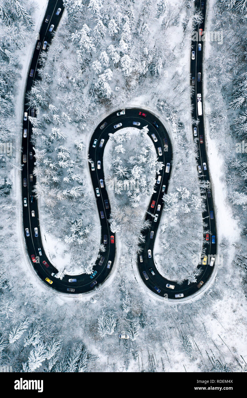 Traffic Jam on a highway trough the mountains. Aerial view of a rush hour traffic after a heavy snowfall. Winter weather and winter traffic conditions Stock Photo