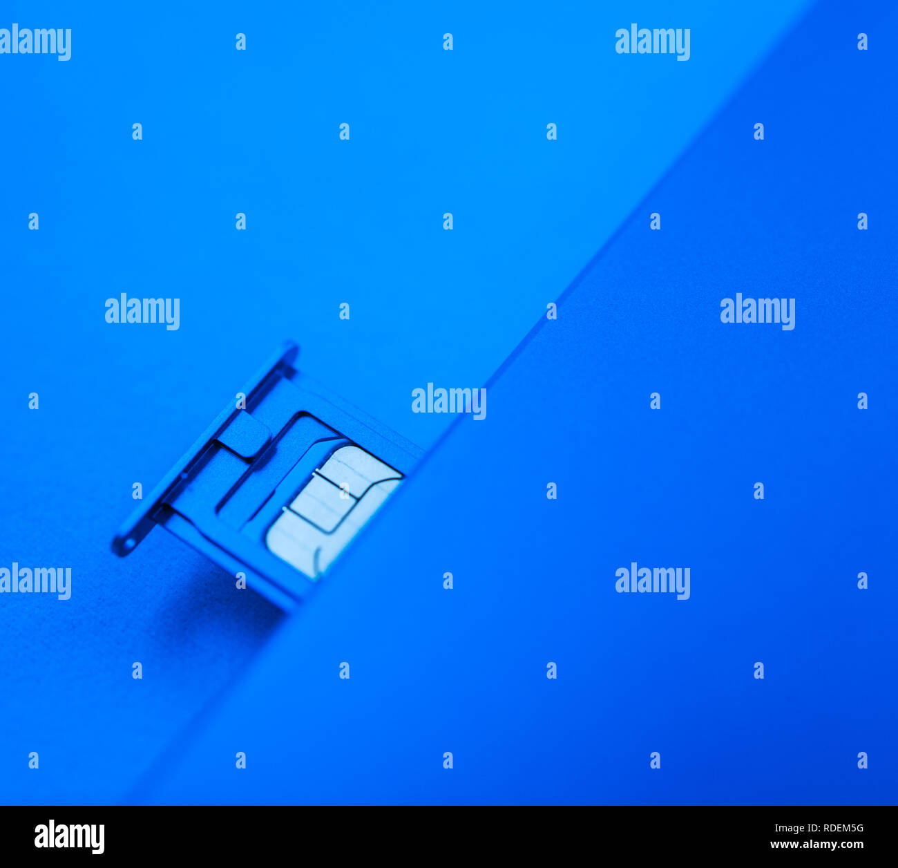 Micro SIM card subscriber identity module inside new smartphone telephone mobile device against blue background - Stock Image