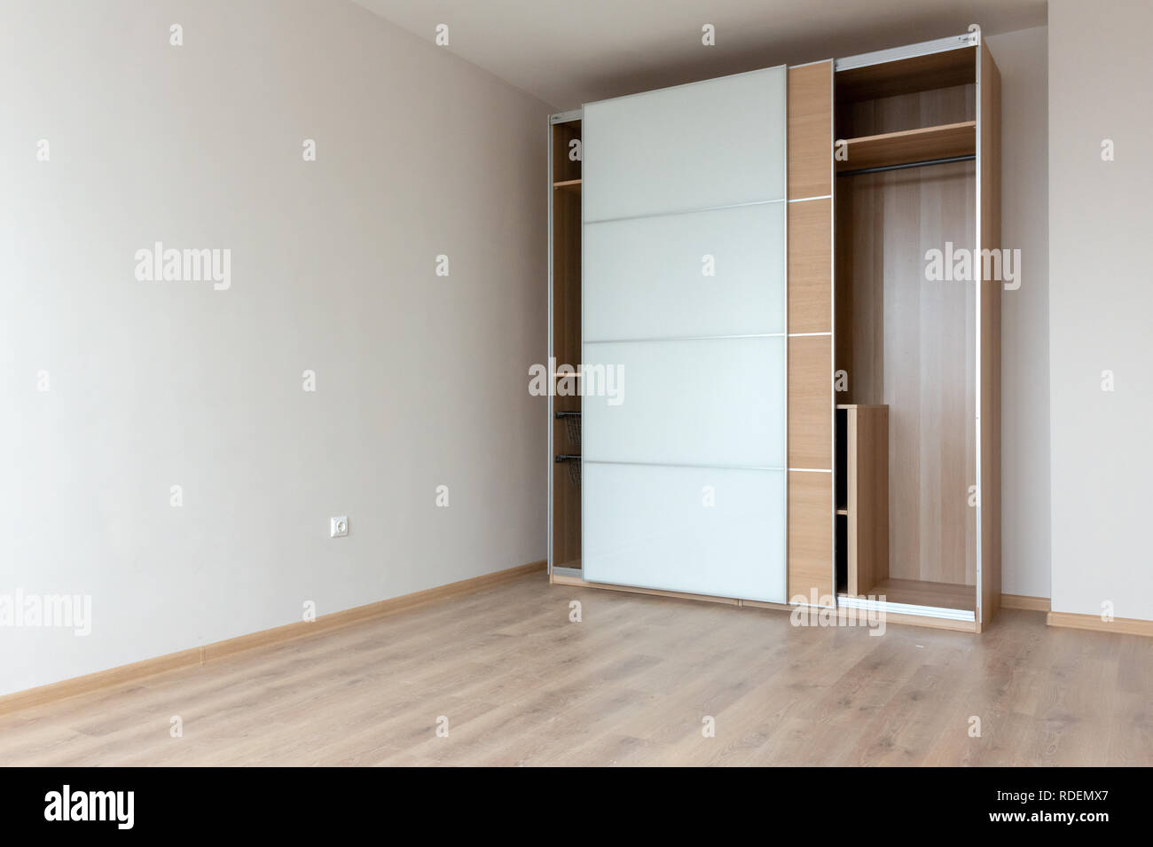 Duotone home interior with empty IKEA wardrobe in semi furnished bedroom. - Stock Image