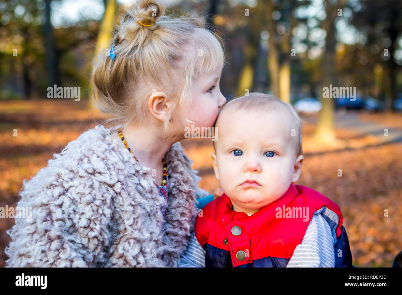 Caucasian young siblings kiss outside in the fall and autumn with leaves - Stock Image