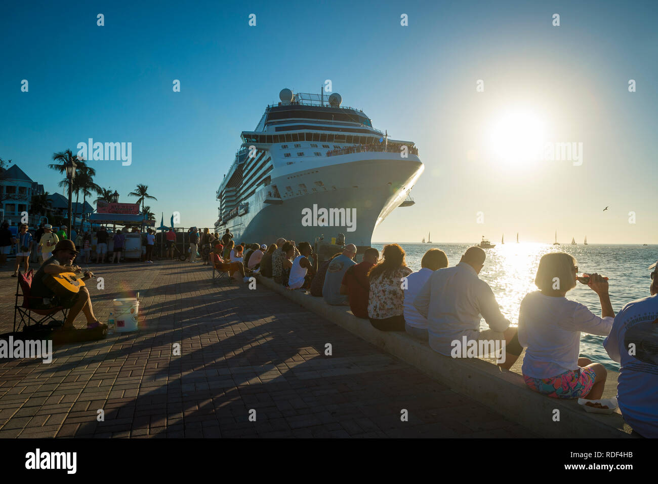 KEY WEST, FLORIDA, USA - JANUARY 13, 2019: Visitors gather under the hulk of a cruise ship at Mallory Square, a bustling tourist destination. - Stock Image