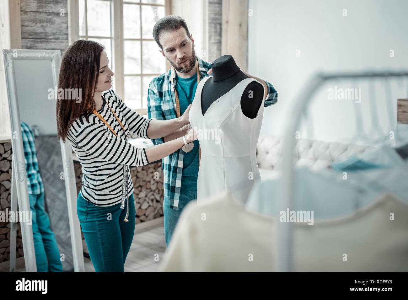 Couple of designers feeling involved in sewing bridal dress - Stock Image