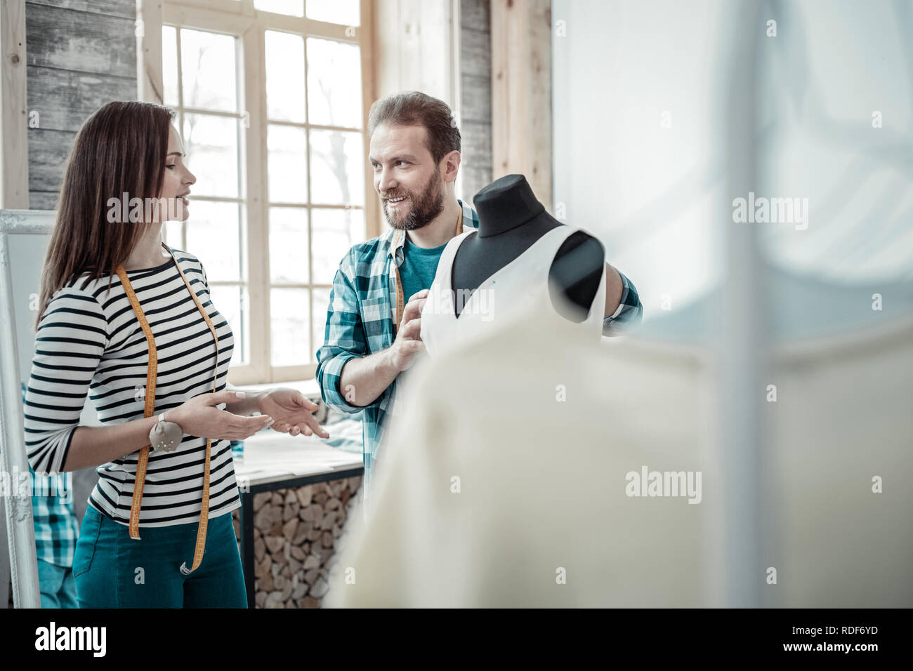 Dark-haired wife designing clothes with her husband - Stock Image