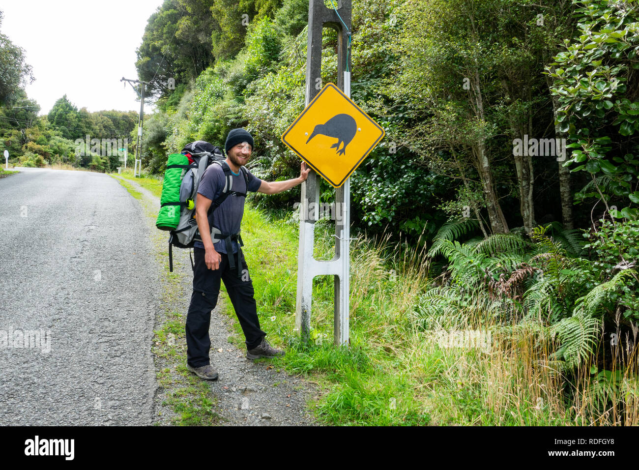 Happy young backpacker with Kiwi bird sign on Stewart Island in New Zealand, popular place with tourists for spotting Kiwi birds. - Stock Image