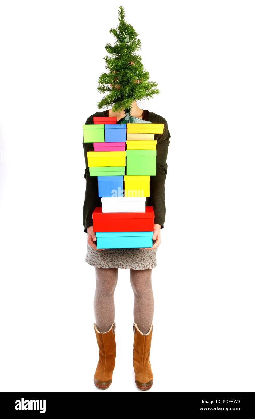 Woman Carrying Cardboard Boxes With Gifts And A Small Christmas Tree