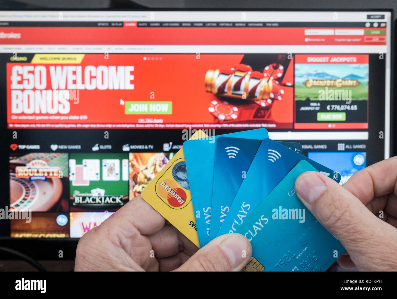 Online gambling. Person holding credit cards with Ladbrokes website on computer sreen in background. - Stock Image