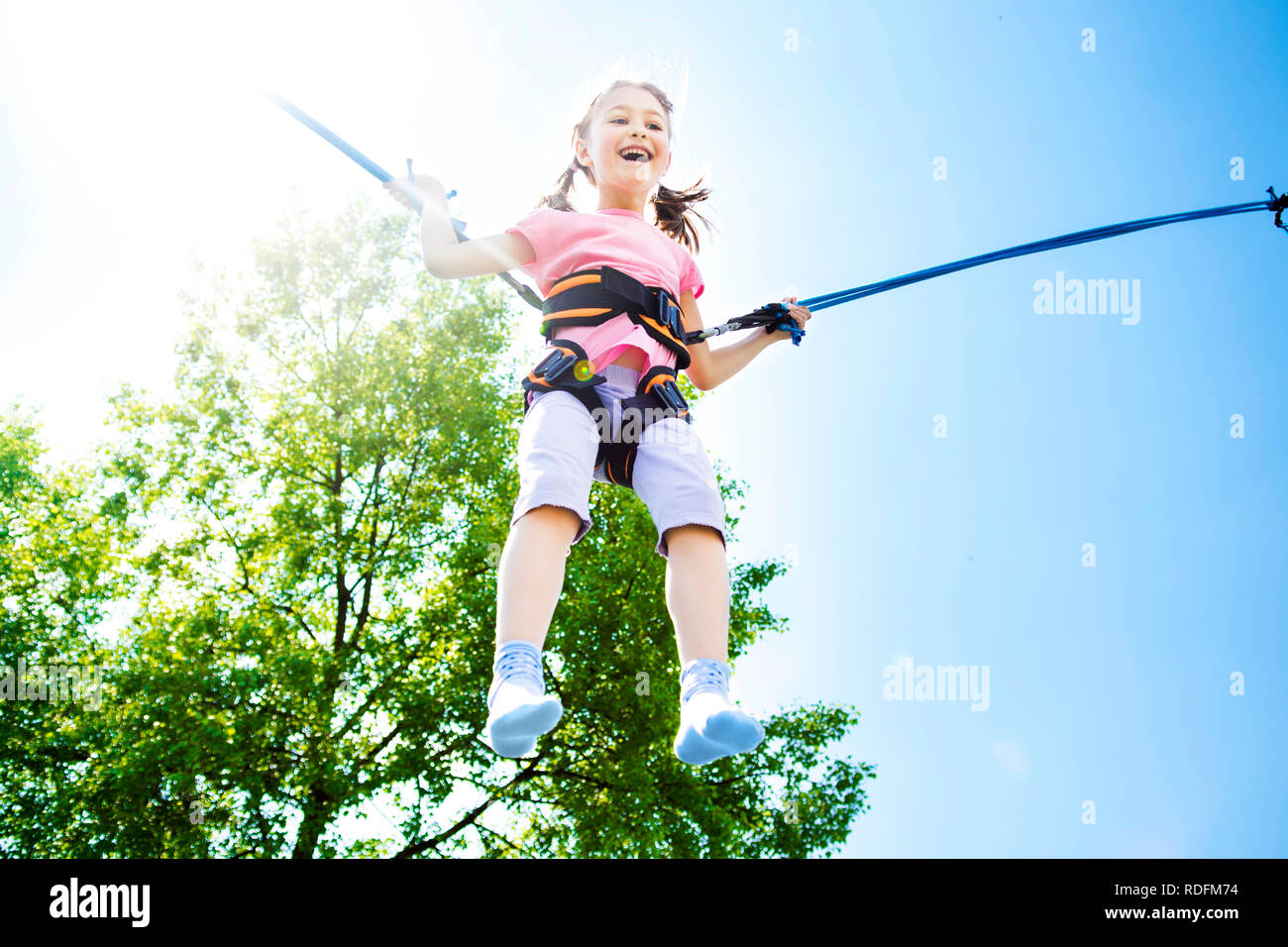 Little girl bouncing high in the air using a bungee trampoline. - Stock Image