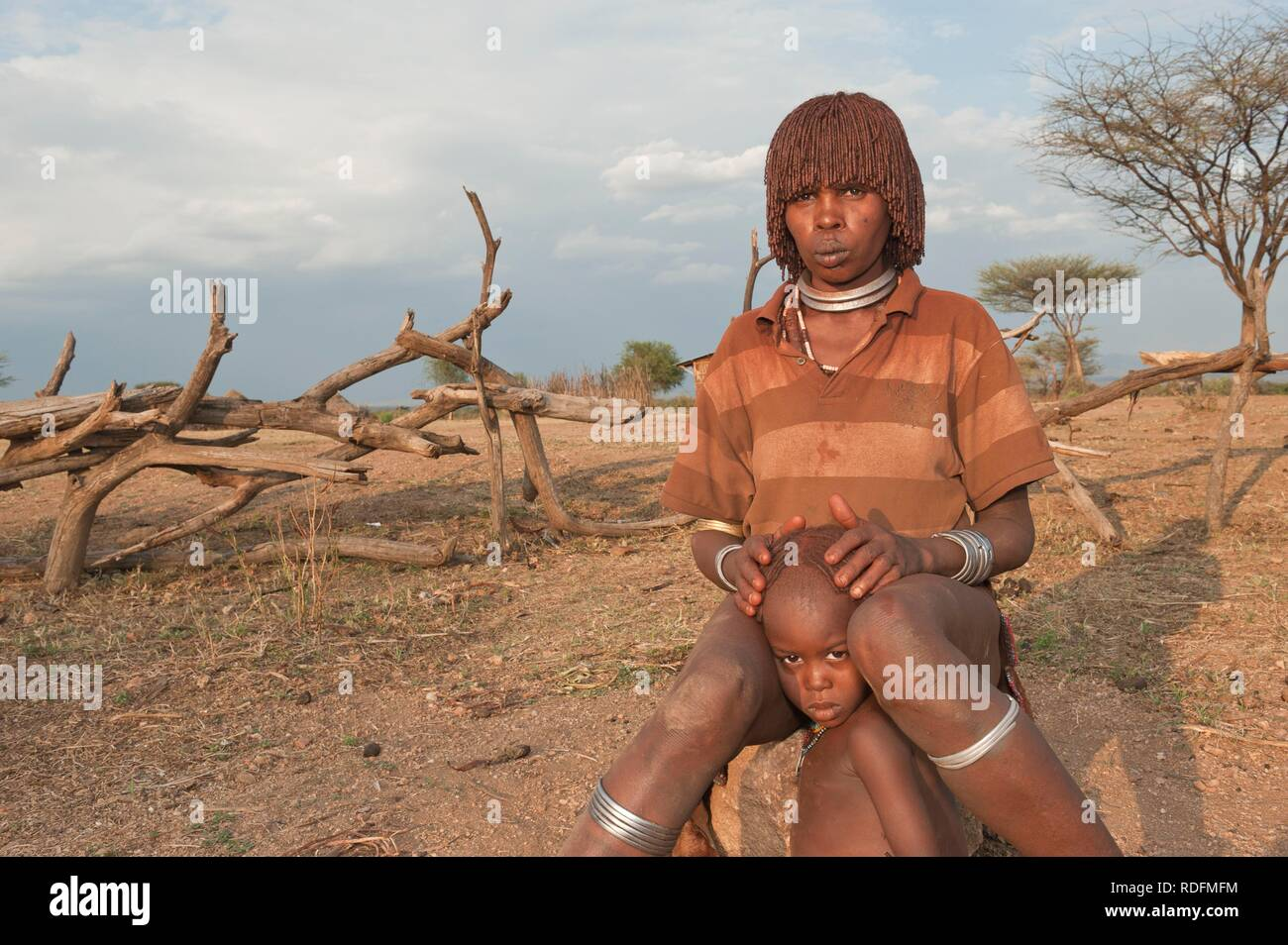 Young Hamar woman with traditional hairstyle with red clay in her hair and with her child, Omo river valley, Southern Ethiopia Stock Photo