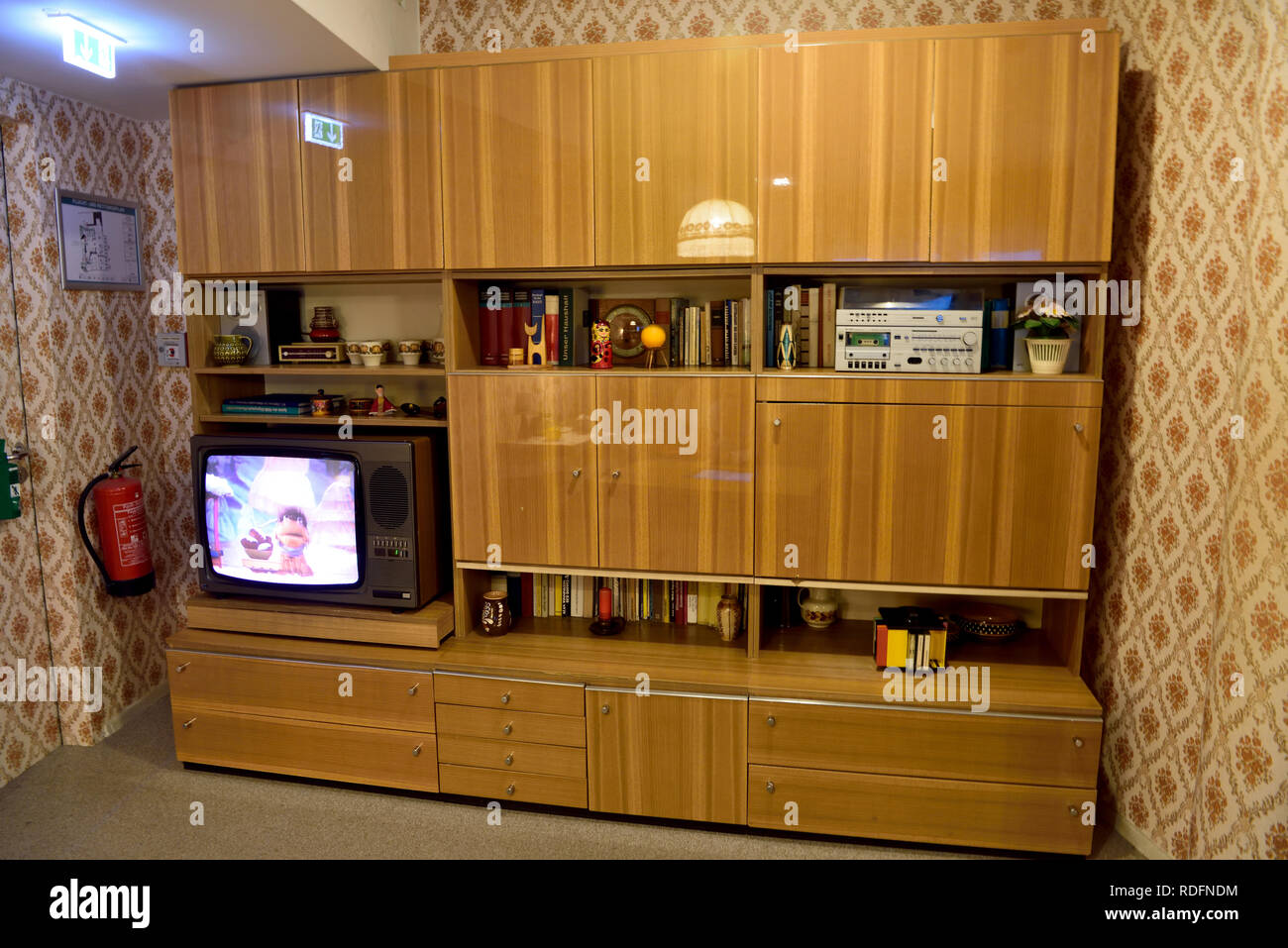Berlin, Germany - November 10, 2018. Typical Soviet-style cupboard on display at DDR Museum in Berlin, with book, TV and souvenirs. - Stock Image