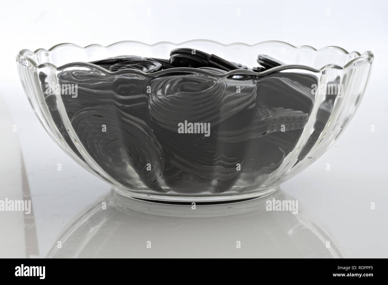 licorice wheels in glass bowl from below - Stock Image