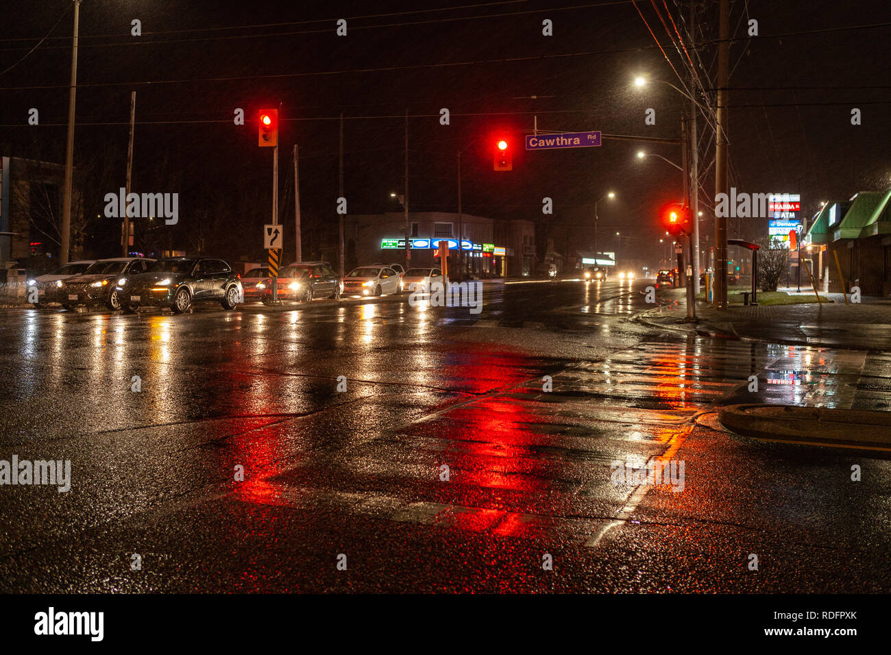 Toronto, CANADA - December 4th, 2019: Dramatic rainy night with empty streets and reflecting traffic lights in lonly city suburbia roads - Stock Image