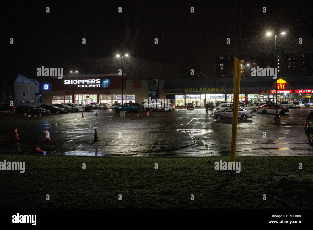 Toronto, CANADA - December 4th, 2019: Dramatic rainy night with deserted streets and reflecting traffic lights by illuminated shop  store - Stock Image
