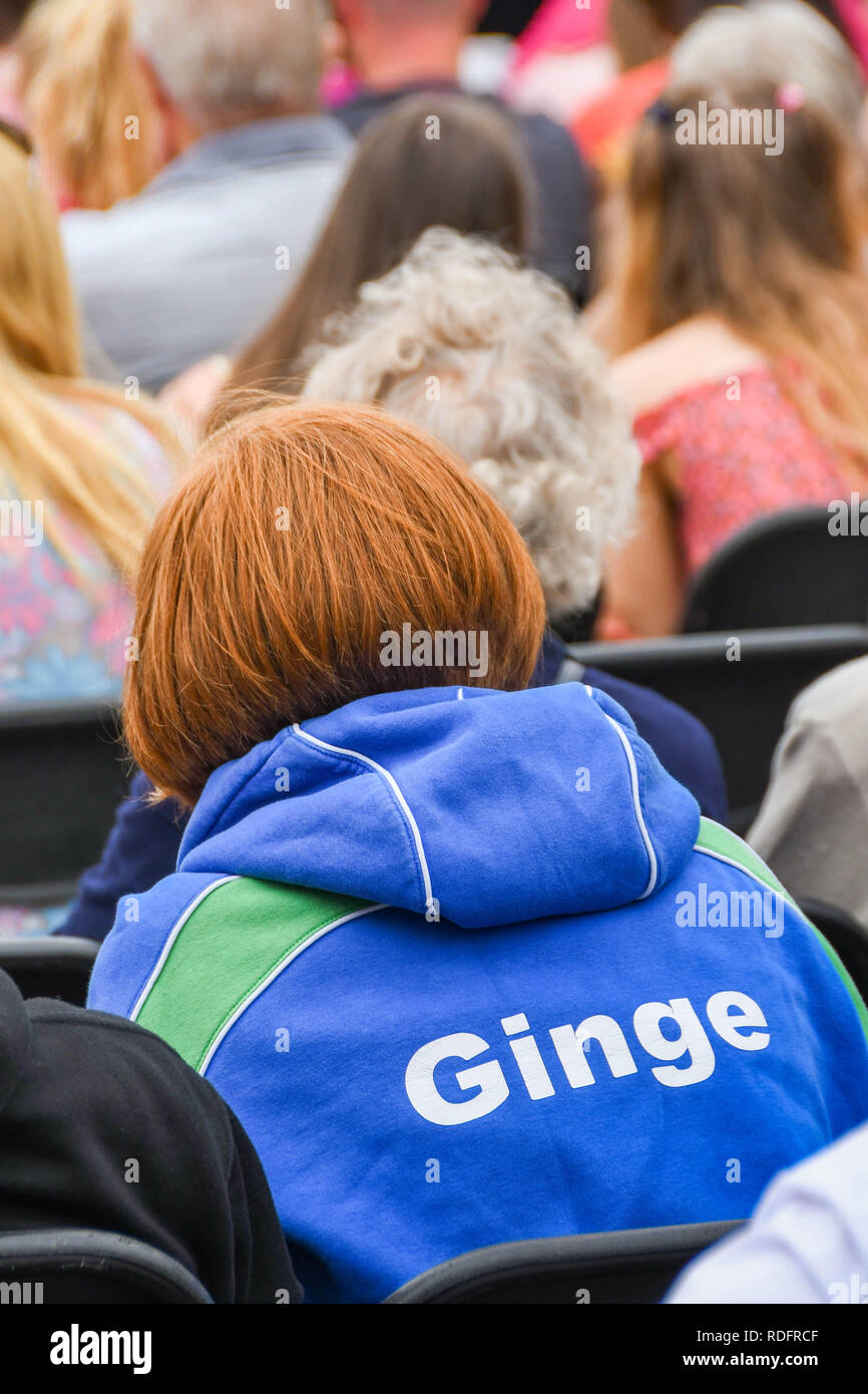 BUILTH WELLS, WALES - JULY 2018: Person with ginger hair wearing a hooded sweatshirt with 'Ginge' nickname on the back. - Stock Image