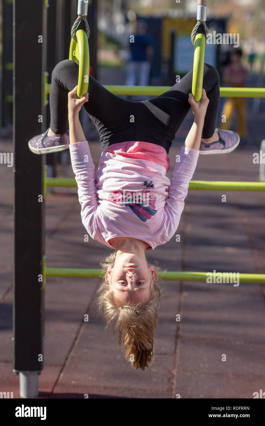 Young girl exercising on gymnastic rings upside down position outside on a playground - Stock Image