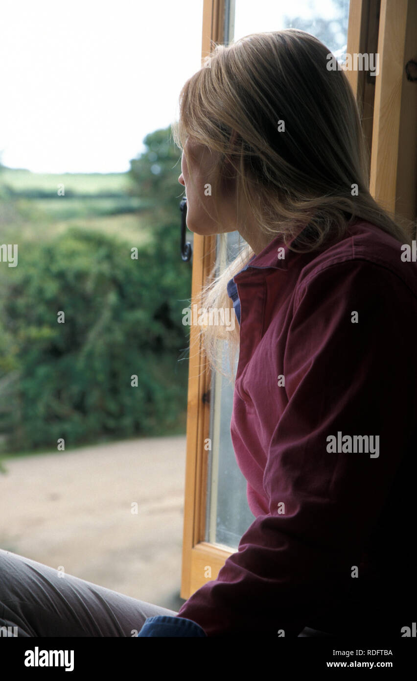 unhappy young woman looking out of bedroom window across rural landscape - Stock Image