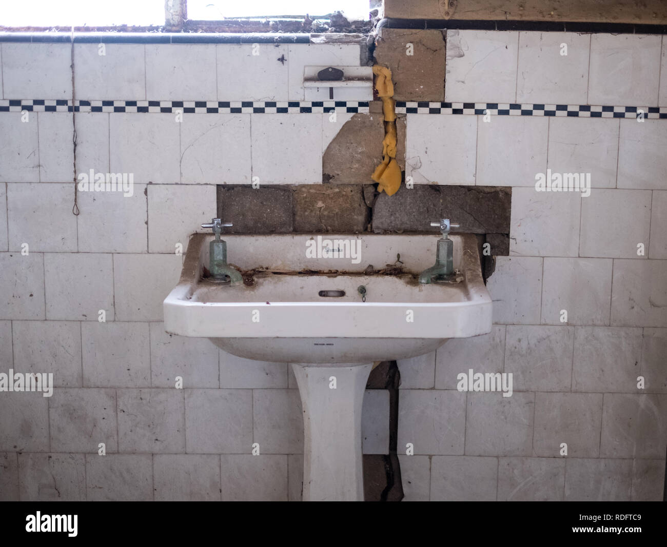 Close up of Shanks hand basin and original tiles in derelict deco style house. House is due for demolition. Rayners Lane, Pinner, Middlesex, UK - Stock Image